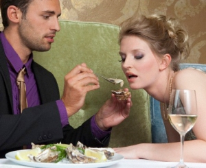 Man feeding girlfriend oysters --- Image by © Judith Haeusler/cultura/Corbis